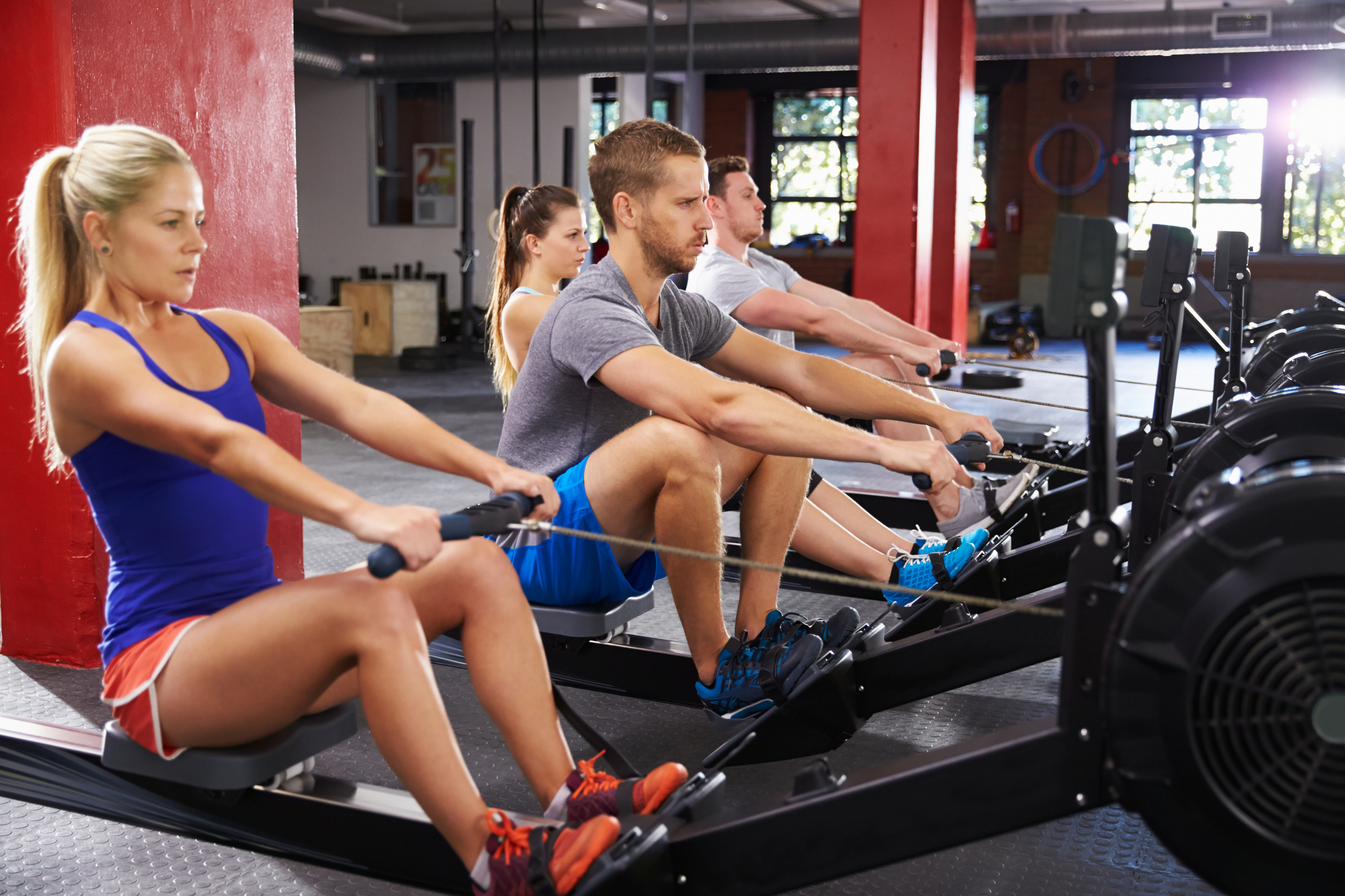 Gym Class Working Out On Rowing Machines Together